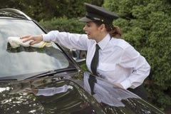Woman chauffeur polishing car window Royalty Free Stock Photos