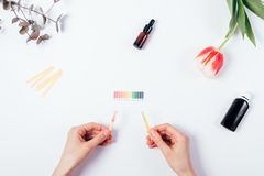 Woman check cosmetics pH level by using litmus paper. And rating scale. Top view of female hands comparison reaction color on white background Stock Image