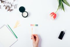 Woman check cosmetics pH level by using litmus paper. And scale. Top view of female hand matching reaction color on white background Stock Photos