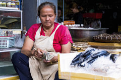Woman check the day`s earnings at Phnom Penh central market, Cambodia Royalty Free Stock Photo