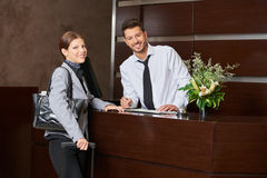 Woman during check-in at hotel reception Stock Photos