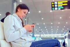 Woman check-in online registration on her mobile phone in airport hall, side view. royalty free stock image