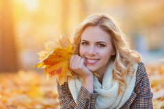 Woman in checked coat sitting in autumn park Stock Photography