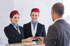 Check in at airport. Woman in checkin counter taking passport for verification from passenger man. Happy smiling hostess at check in working with her colleague royalty free stock photos