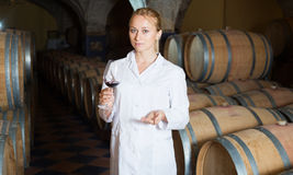 Woman checking ageing process of wine. Serious blonde woman in white robe checking ageing process of red wine royalty free stock photo
