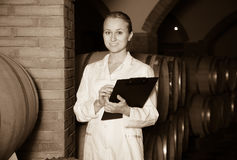 Woman checking ageing process of wine Royalty Free Stock Image