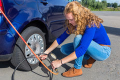 Woman checking air pressure of car tire Royalty Free Stock Images