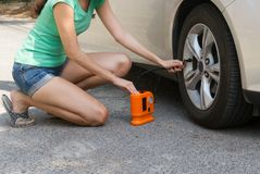 Woman checking air tyre pressure with air pressure guage stock photo