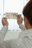 Woman checking banknote watermark Royalty Free Stock Image