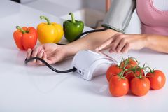 Woman Checking Blood Pressure On Table. Close-up Of A Woman Checking Blood Pressure On Table With Vegetables stock image
