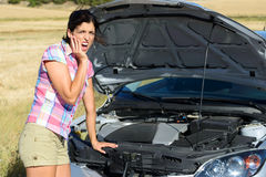 Woman checking broken car engine. Upset woman after car accident or broken down engine waiting for insurance road assistance service help Royalty Free Stock Images