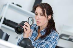 Woman checking camera lense using magnifying glass Royalty Free Stock Photos