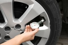 Woman checking car tire pressure with air gauge stock image