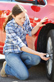 Woman Checking Car Tyre Pressure Using Gauge. Woman Checking Car Tyre Pressure Royalty Free Stock Photo