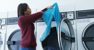 Woman checking clothes after washing in washing machine 4k. Woman checking clothes after washing in washing machine at laundromat 4k stock footage