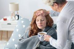 Woman checking daughter`s body temperature Stock Photos