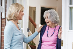 Woman Checking On Elderly Female Neighbor Stock Photography