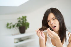 Woman checking the end of her hair for split ends Stock Photo