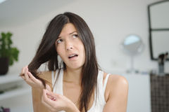 Woman checking the end of her hair for split ends Royalty Free Stock Photography