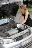 Woman checking engine oil level Stock Images