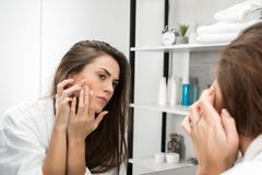 Woman checking face skin. And looking at the mirror in the bathroom stock photo