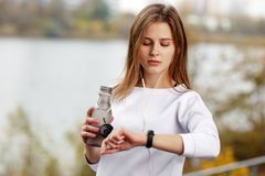 Woman checking fitness and health tracking wearable device. Woman checking fitness and health tracking wearable device Royalty Free Stock Photo