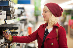 Woman checking food item in store. Woman checking labeling on food item in store Royalty Free Stock Photos