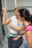 Woman checking friend's muscles at changing room Royalty Free Stock Photography