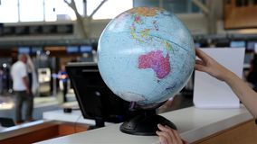Woman checking globe map at information desk inside YVR airport stock video footage
