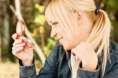 Woman checking hair in mirror. Blond woman checking hair in mirror, outdoor Royalty Free Stock Photos