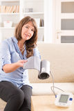 Woman checking her blood pressure Royalty Free Stock Images