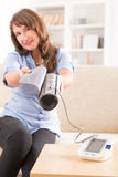 Woman checking her blood pressure Royalty Free Stock Image
