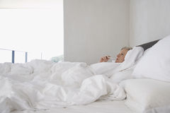 Woman Checking Her Body Temperature In Bed Royalty Free Stock Image