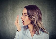 Woman checking her breath with hand. stock image