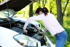 Woman checking her car engine. Beautiful woman checking her car engine Royalty Free Stock Photography