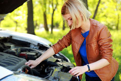 Woman checking her car engine Royalty Free Stock Image