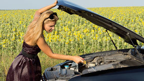 Woman checking her engine oil Stock Photo