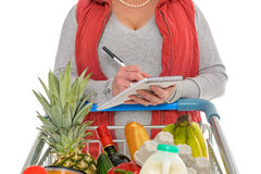 Woman checking her food shopping list. A woman checking her shopping list with a trolley full of fresh food, isolated on a white background Stock Photography