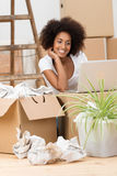Woman checking her laptop on a cardboard box Stock Photo