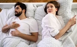 Woman checking her mobile while her husband sleeping on bed in bedroom royalty free stock photography