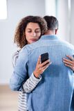 Woman checking her mobile phone while embracing a man Royalty Free Stock Image