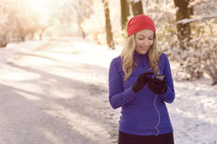 Woman checking her mobile on a winter walk Royalty Free Stock Photos