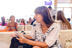 Woman checking her passport in an airport terminal Royalty Free Stock Photos