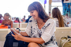 Woman checking her passport in an airport terminal Royalty Free Stock Photography