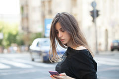 Woman checking her smart phone. Young Woman checking her smart phone on the street Stock Photos