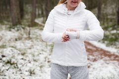 Woman checking her smartwatch during training in forest. In cold weather Royalty Free Stock Photography