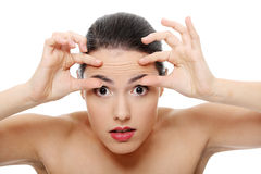 Woman checking her wrinkles on her forehead Stock Images
