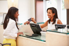 Woman Checking In At Hotel Reception Royalty Free Stock Image