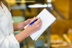 Woman checking list at supermarket Stock Photo