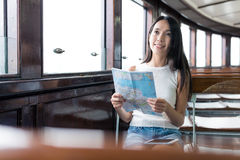 Woman checking location on paper map in ferry. Asian young woman Royalty Free Stock Image